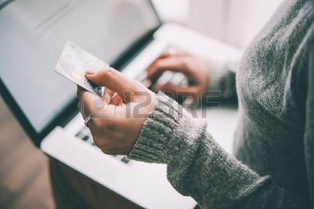 55419076-hands-holding-plastic-credit-card-and-using-laptop-online-shopping-concept-toned-picture